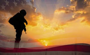 Double exposure Silhouette of Soldier on the United States flag in sunset for Veterans Day is an official USA public holiday